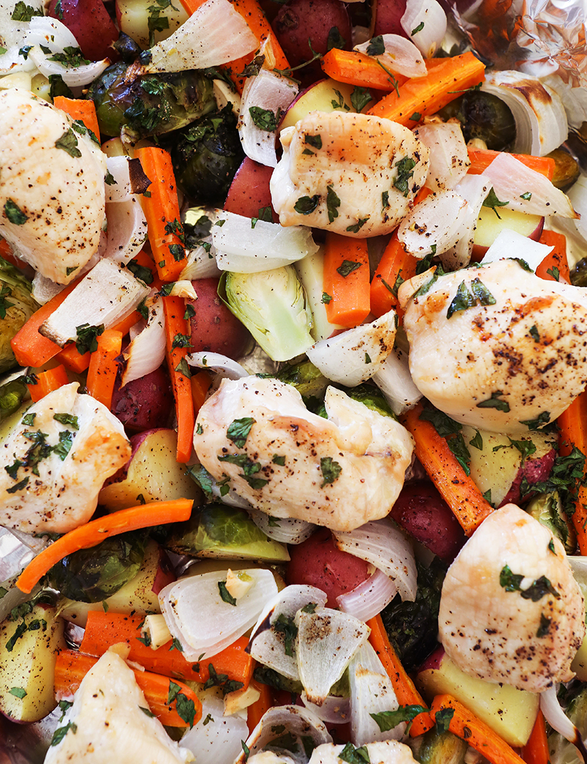 close up top view of sheet pan filled with cooked chicken and vegetables