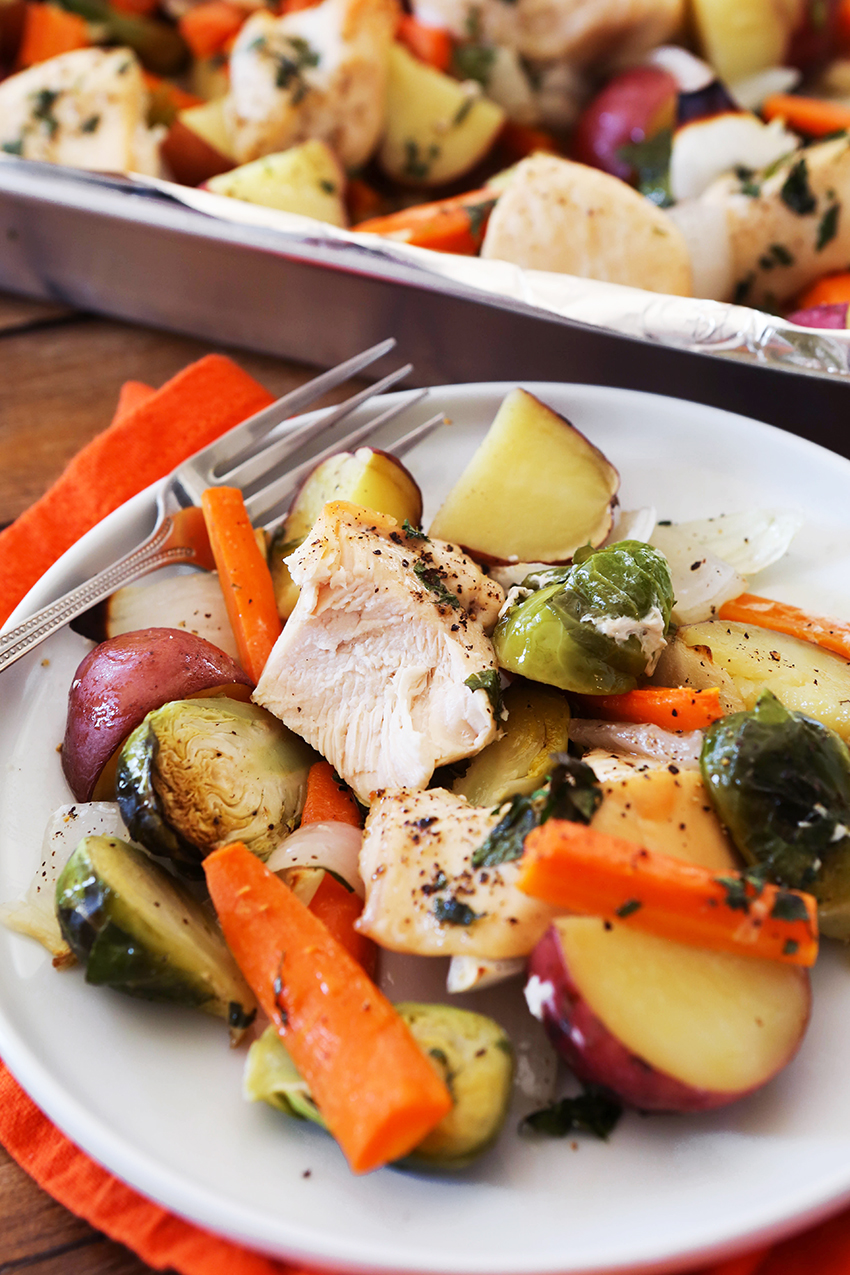 roasted chicken and vegetables on a plate, chicken cut into