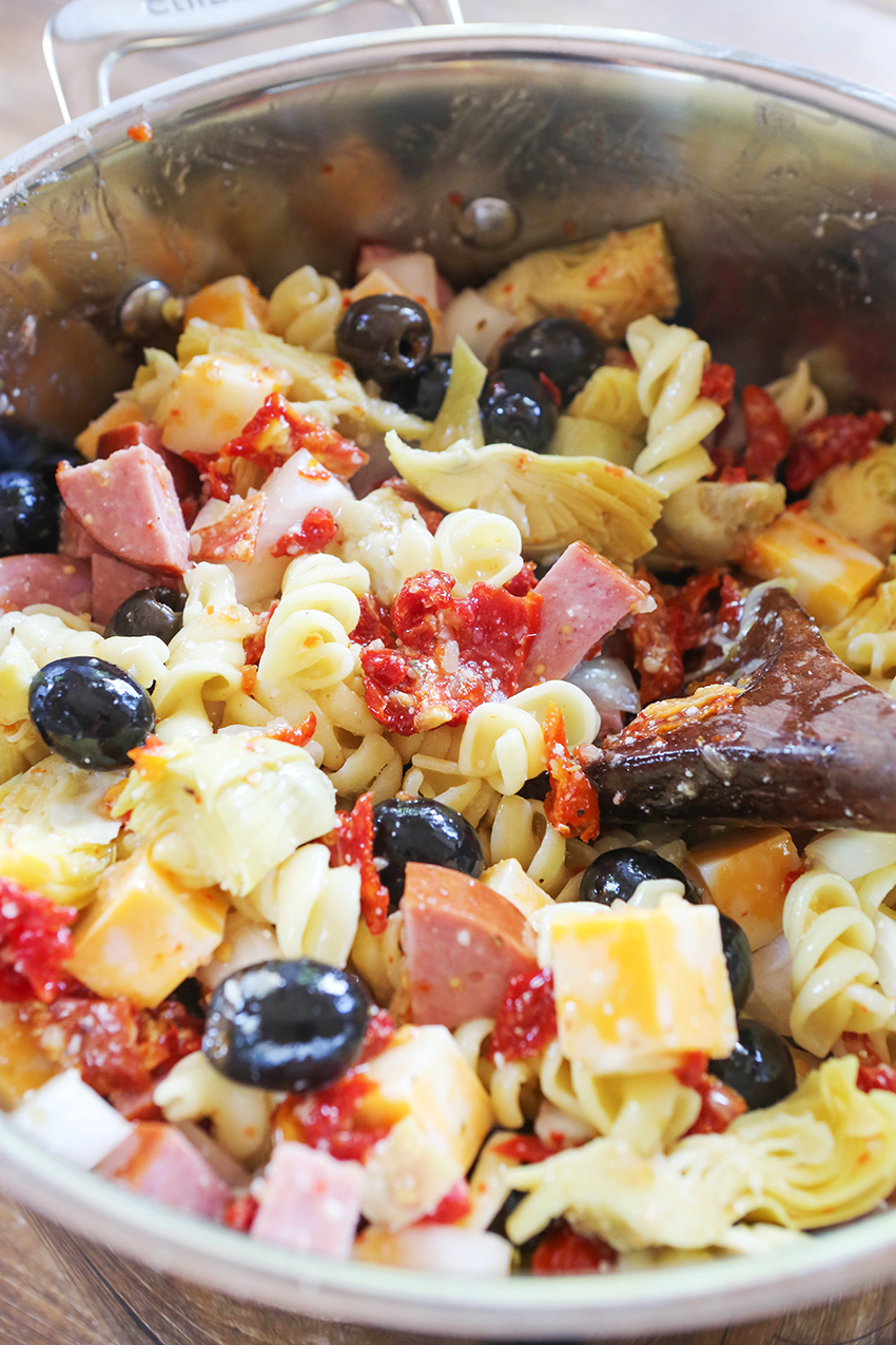larget saucepan filled with pasta salad with a wooden spoon sticking out of it