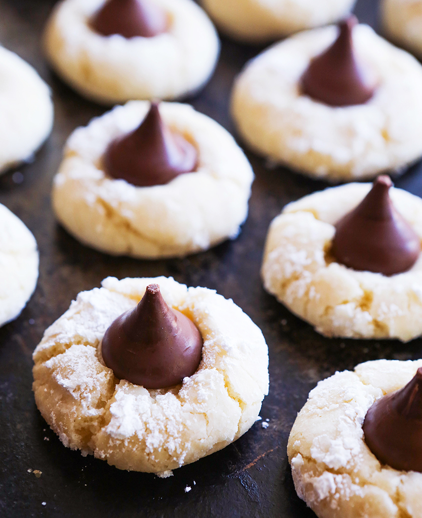 cream cheese cookies on baking sheet with chocolate kisses in centers