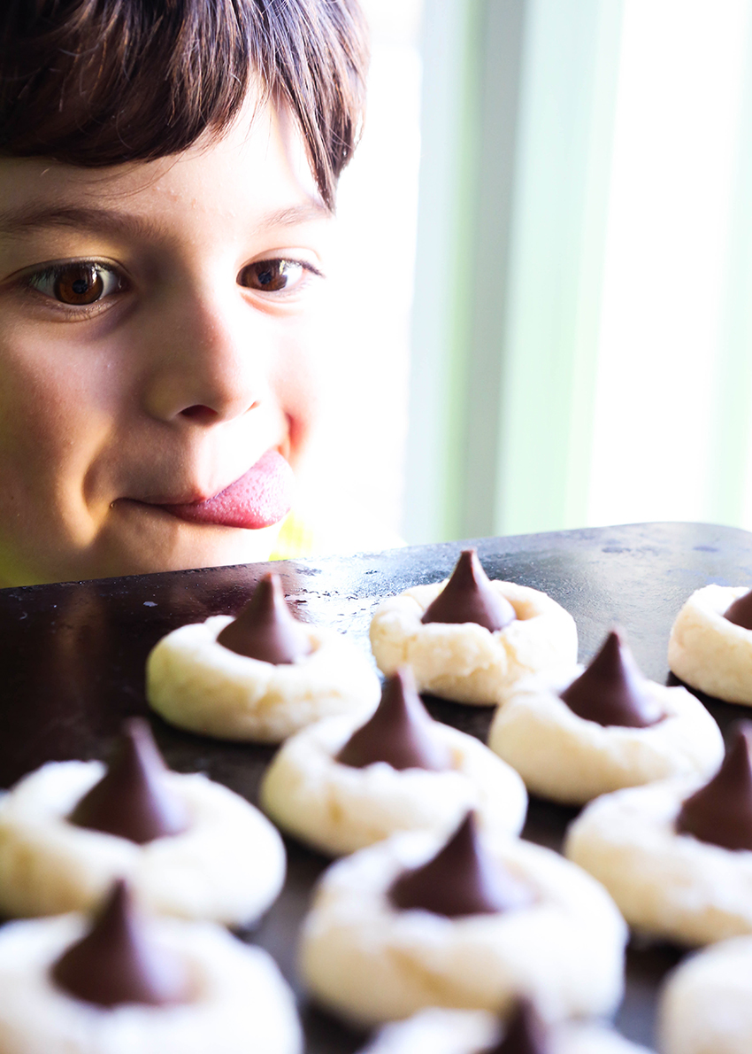 cute boy staring longingly at a tray of cream cheese cookies