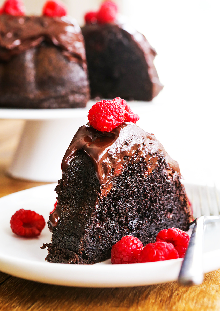 perfect piece of chocolate cake on a white plate topped with fresh raspberries