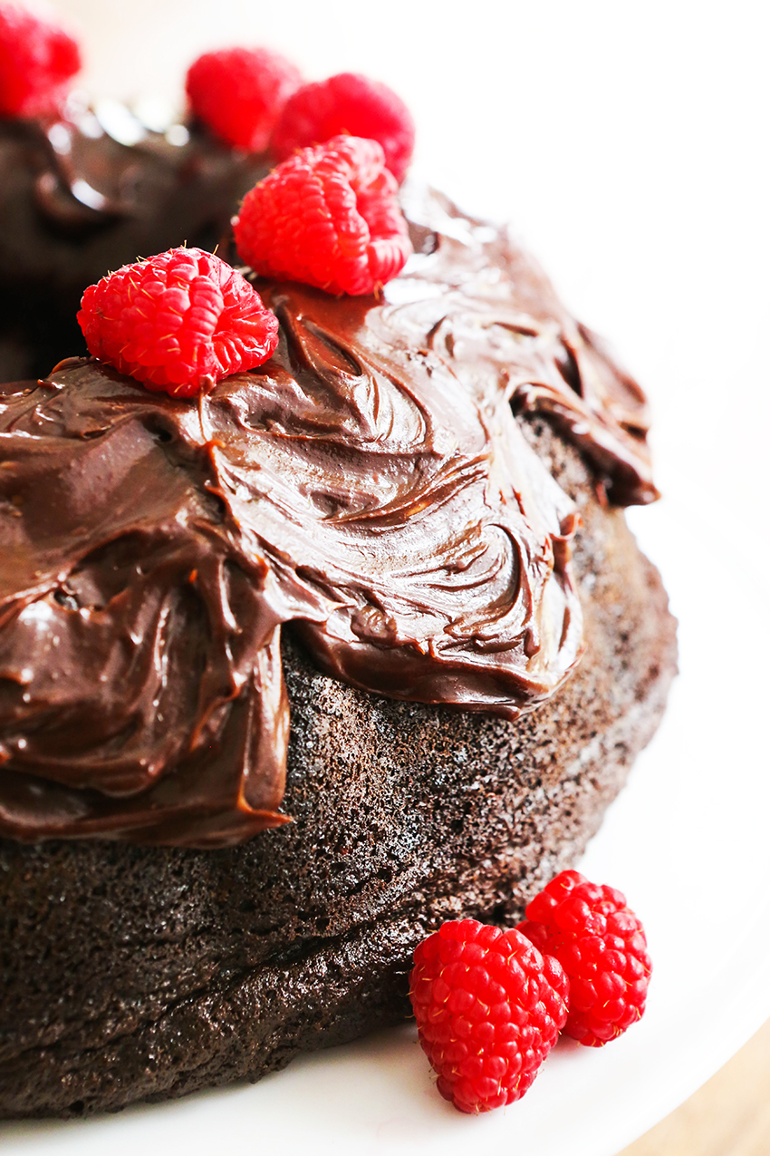 Chocolate bundt cake topped with chocolate frosting and topped with fresh raspberries