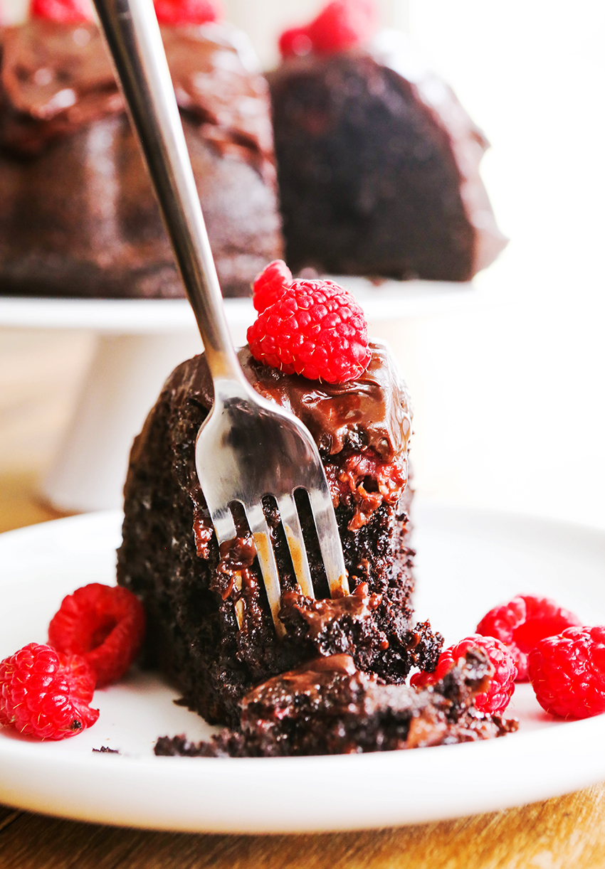 Fork stuck into a piece of chocolate cake with raspberries around it