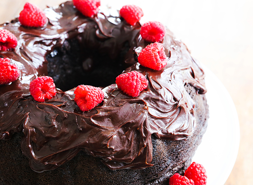 top view of a chocolate bundt cake with chocolate frosting and raspberries