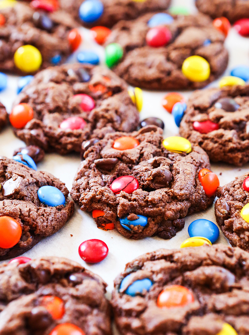 chocolate M&M cookies lined up on a baking sheet with M&M's scattered