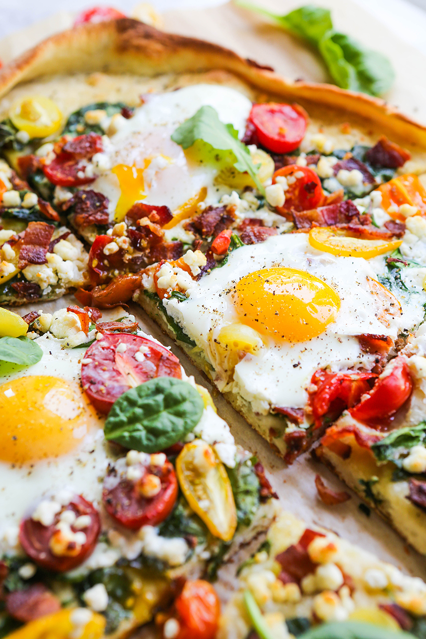 breakfast pizza with over-easy egg and tomatoes on top