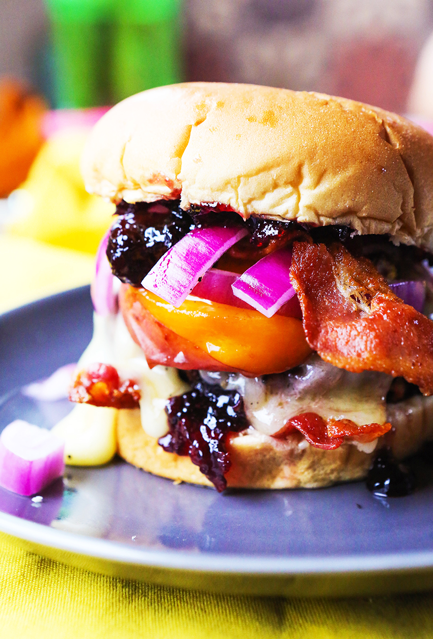 A side view of a grilled burger on a bun with grilled peaches, cherry and brie jam and bacon on a plate