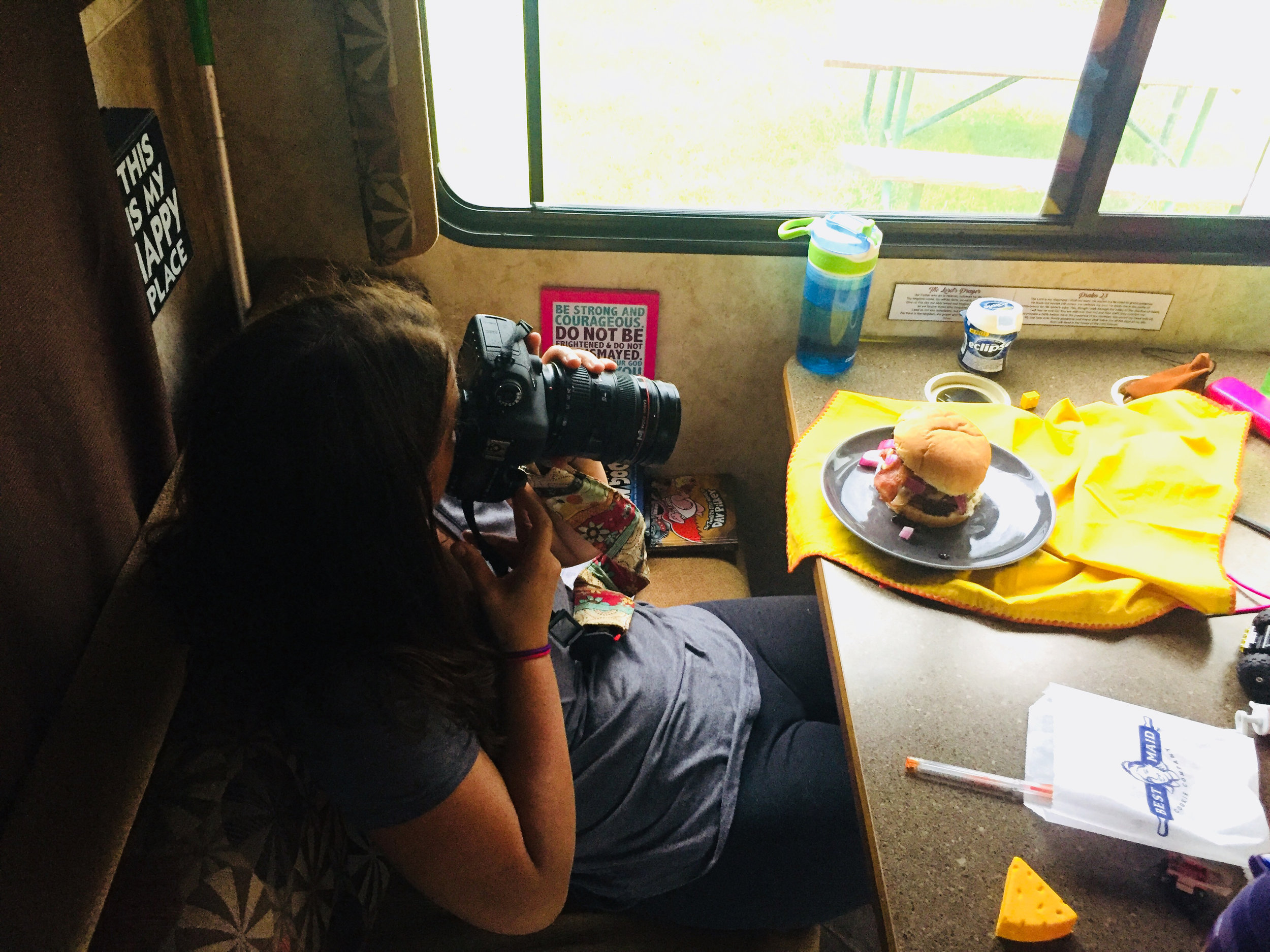 Overhead view of photographer taking a picture of a plated burger with grilled peaches, cherry and brie jam on a plate sitting on a table in an RV.