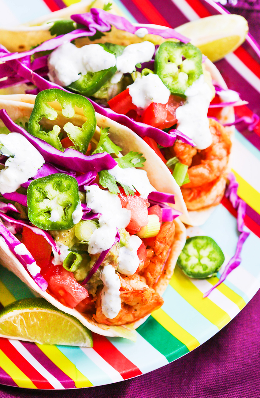 Close up of 2 shrimp tacos drizzled with cilantro lime sauce