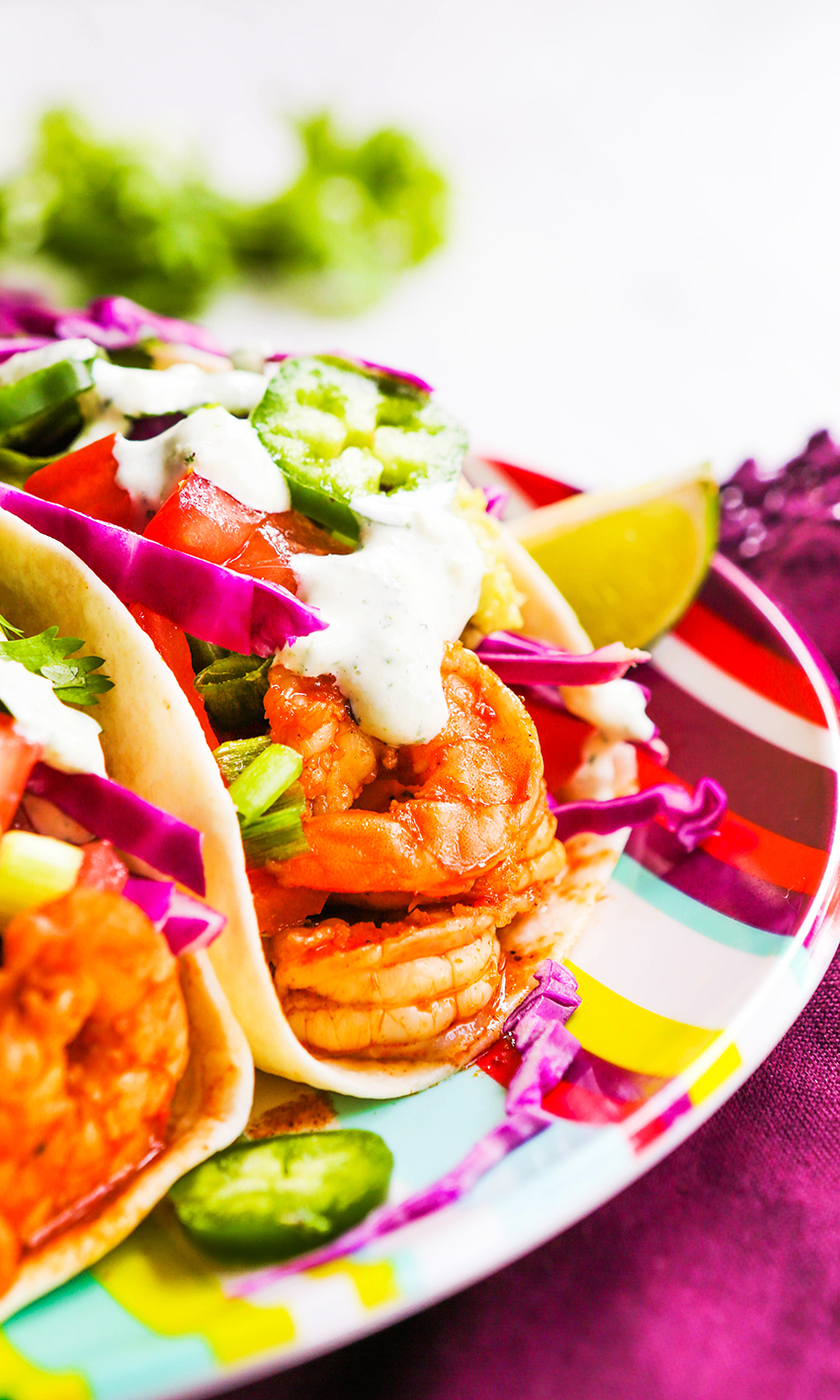close up of 1 shrimp tacos with all the toppings and cilantro lime dressing