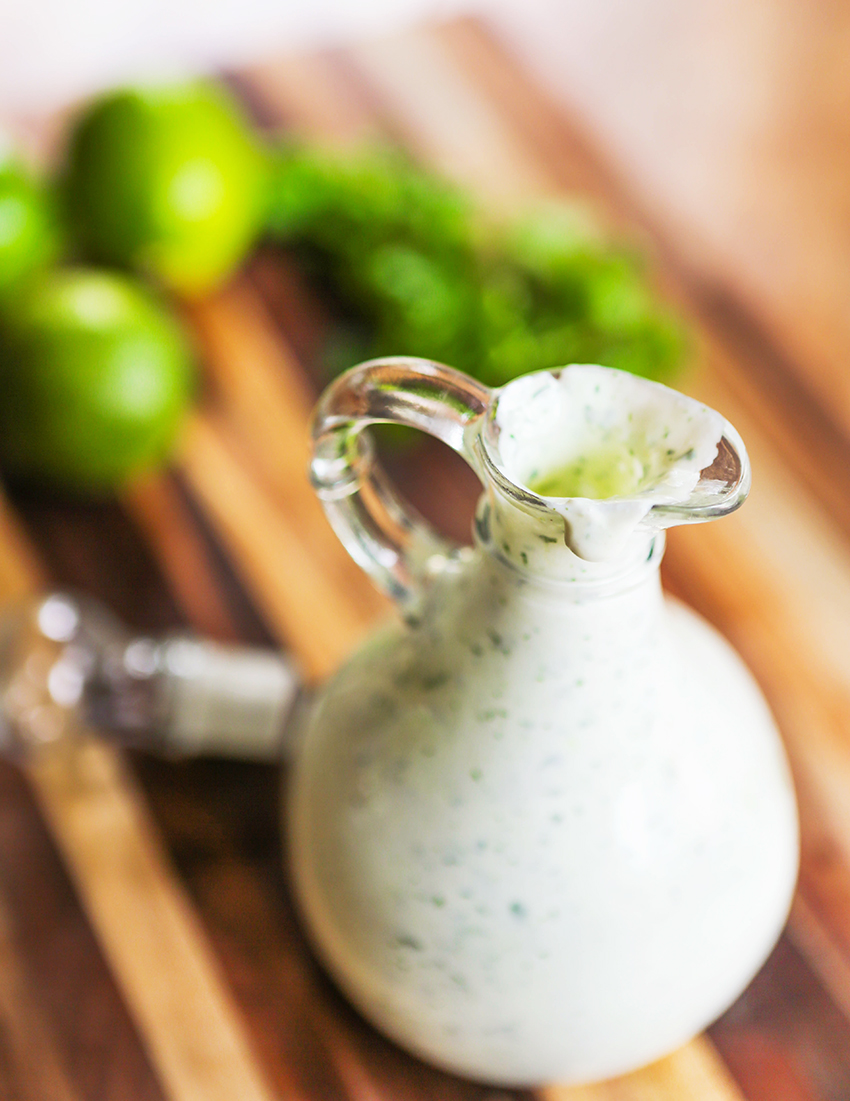 pourable container of cilantro lime sauce with limes nearby