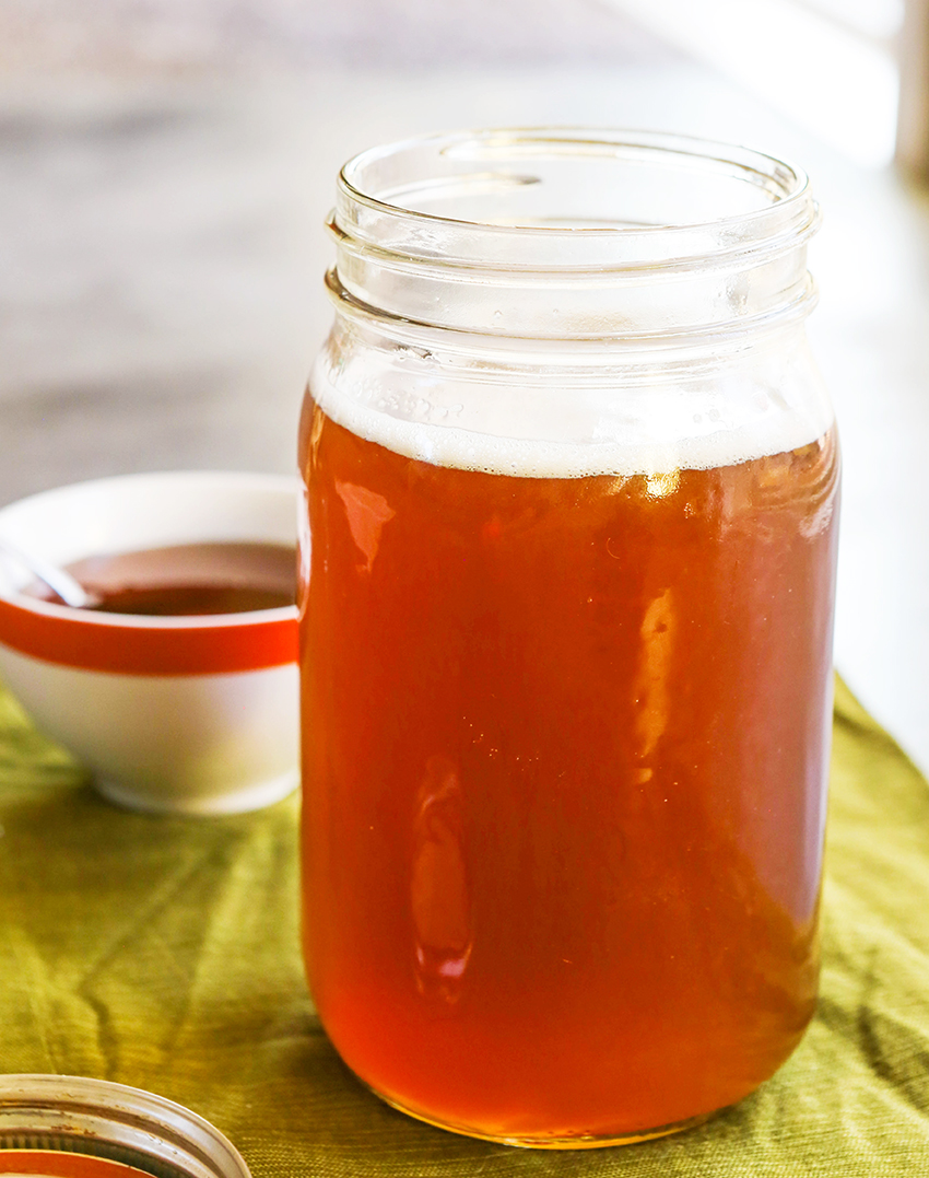 Open glass jar of syrup using honey with a glass of tea in the background