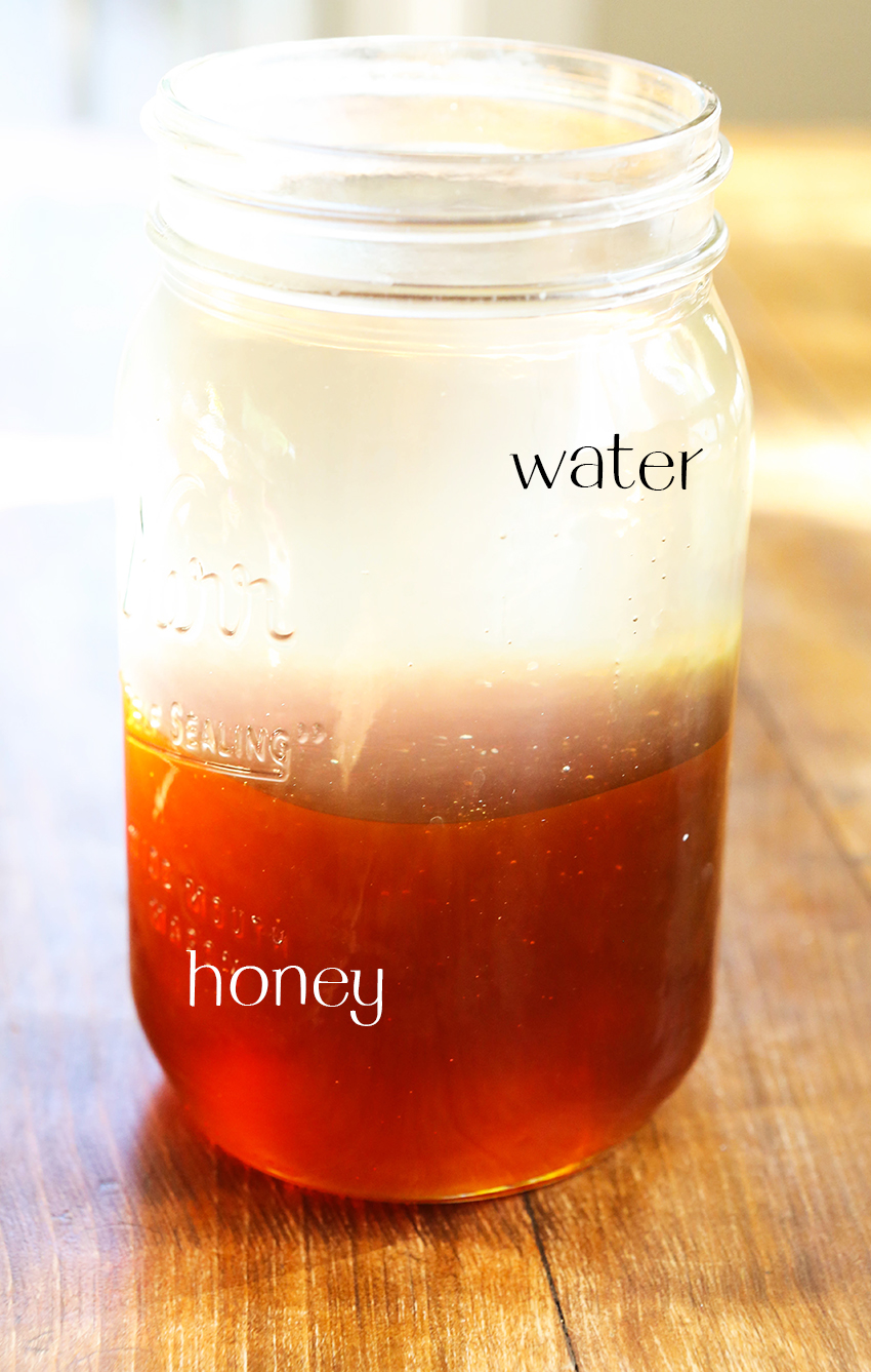 Close up of a glass jar filled with water and honey sitting on a table