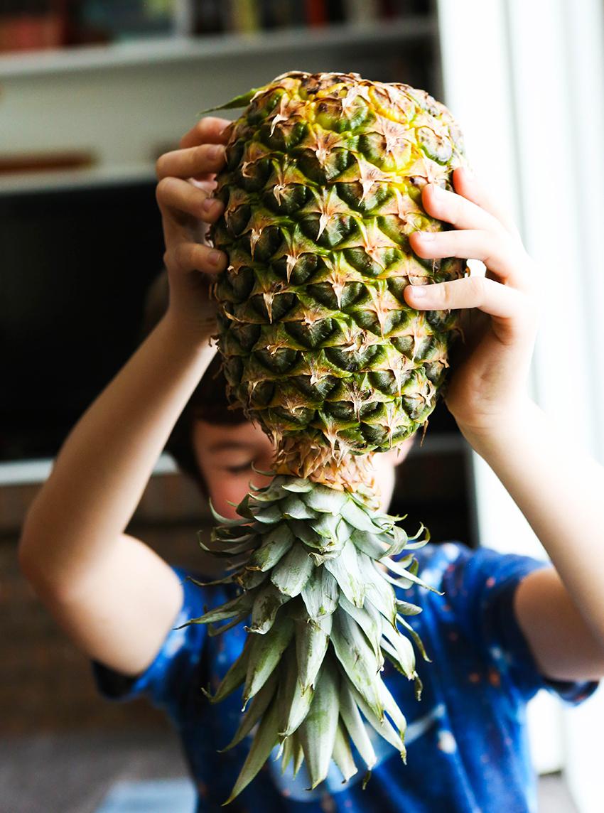cute boy holding a pineapple upside down