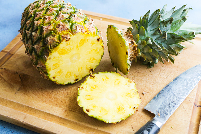 how to cut a pineapple: stem and base removed on a cutting board
