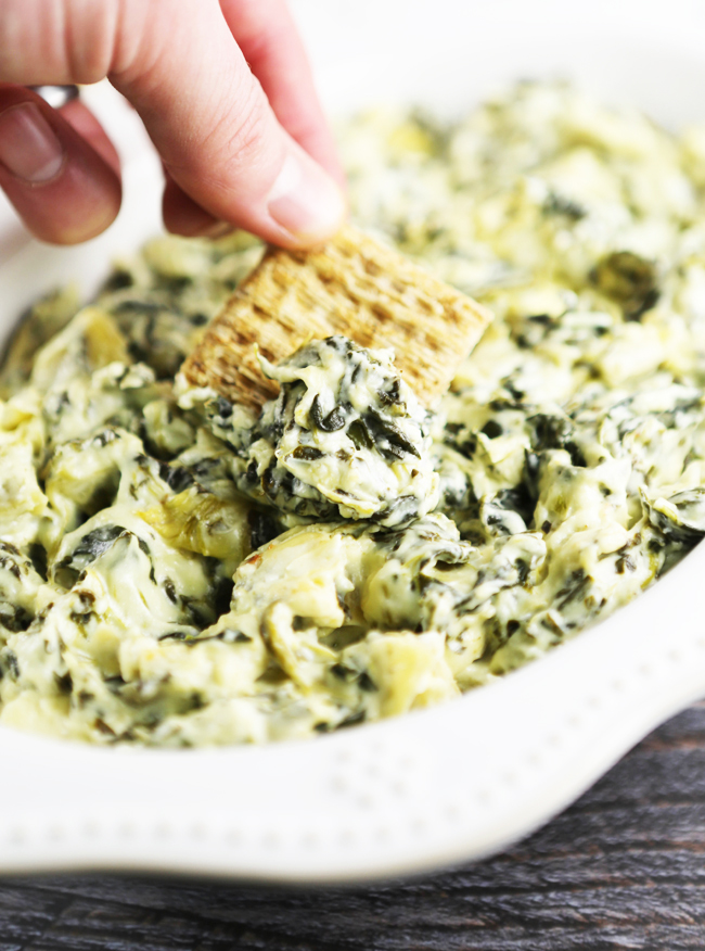 fingers dipping Triscuit into bowl of crockpot spinach artichoke dip
