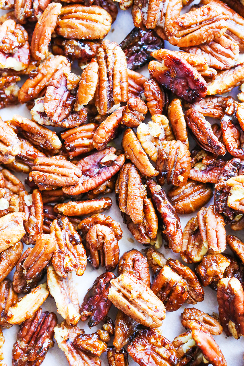close up of stove top candied pecans spread out on a sheet pan.