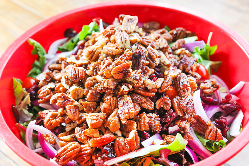 Candied pecans topped over a large bowl of chopped salad