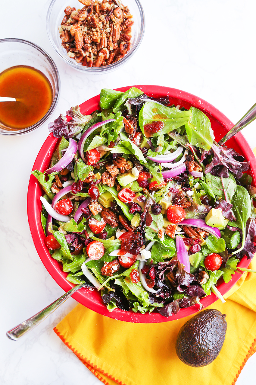 Large red bowl of chopped salad with a two small bowls in the upper corner with dressing and candied pecans