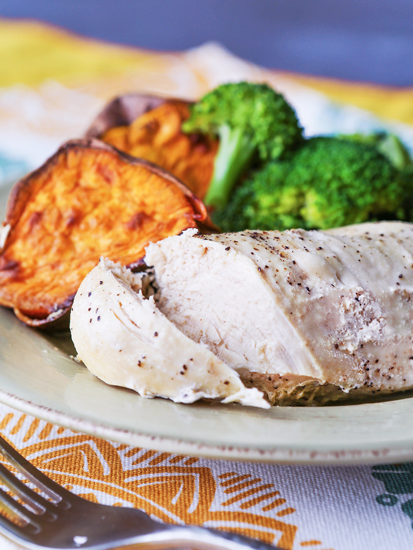 Close up of a cooked chicken breast on a plate with sweet potato and broccoli behind it