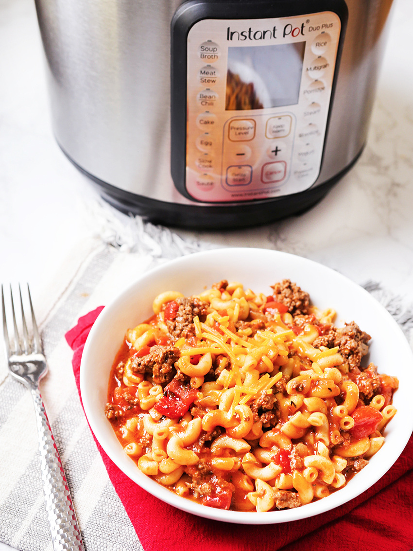 Bowl of goulash sitting next to Instant Pot
