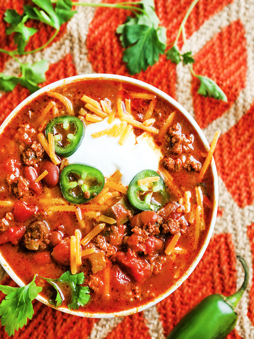 Top view of bowl of chili with melted cheese and jalapeno slices
