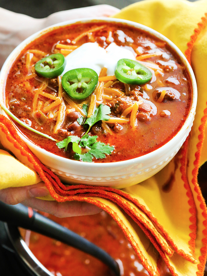 Hands cradling bowl of chili with toppings