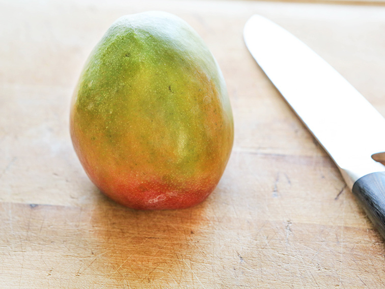 A mango sitting up on the the base of the mango that was just cut off and the knife sitting next to it