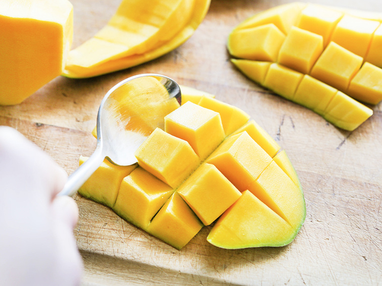 A spoon scooping up a sliced piece of mango away from the flesh of the fruit sitting on a cutting board
