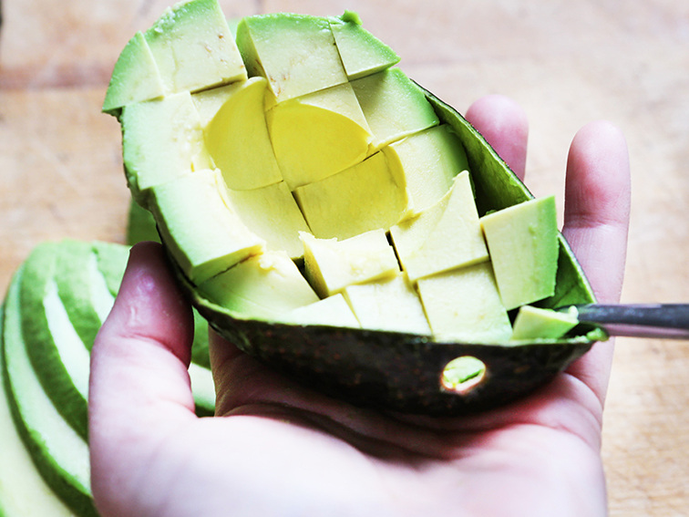 A hand holding half an avocado with the fruit diced into pieces inside the skin