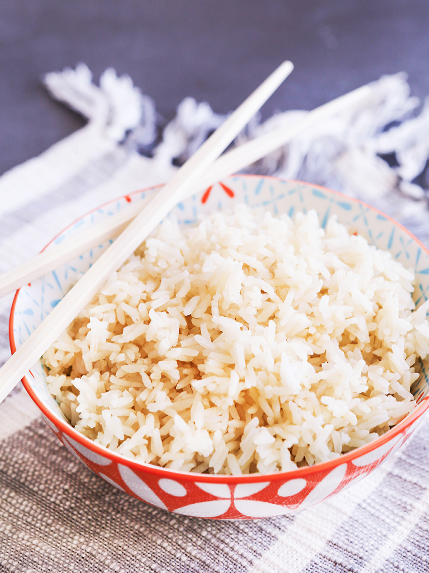 bowl of white rice with chop sticks sitting over the edge
