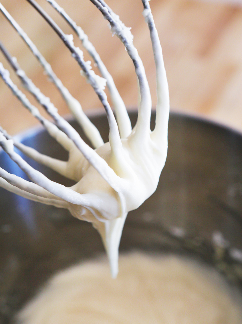 Whisk with frosting dripping into mixing bowl