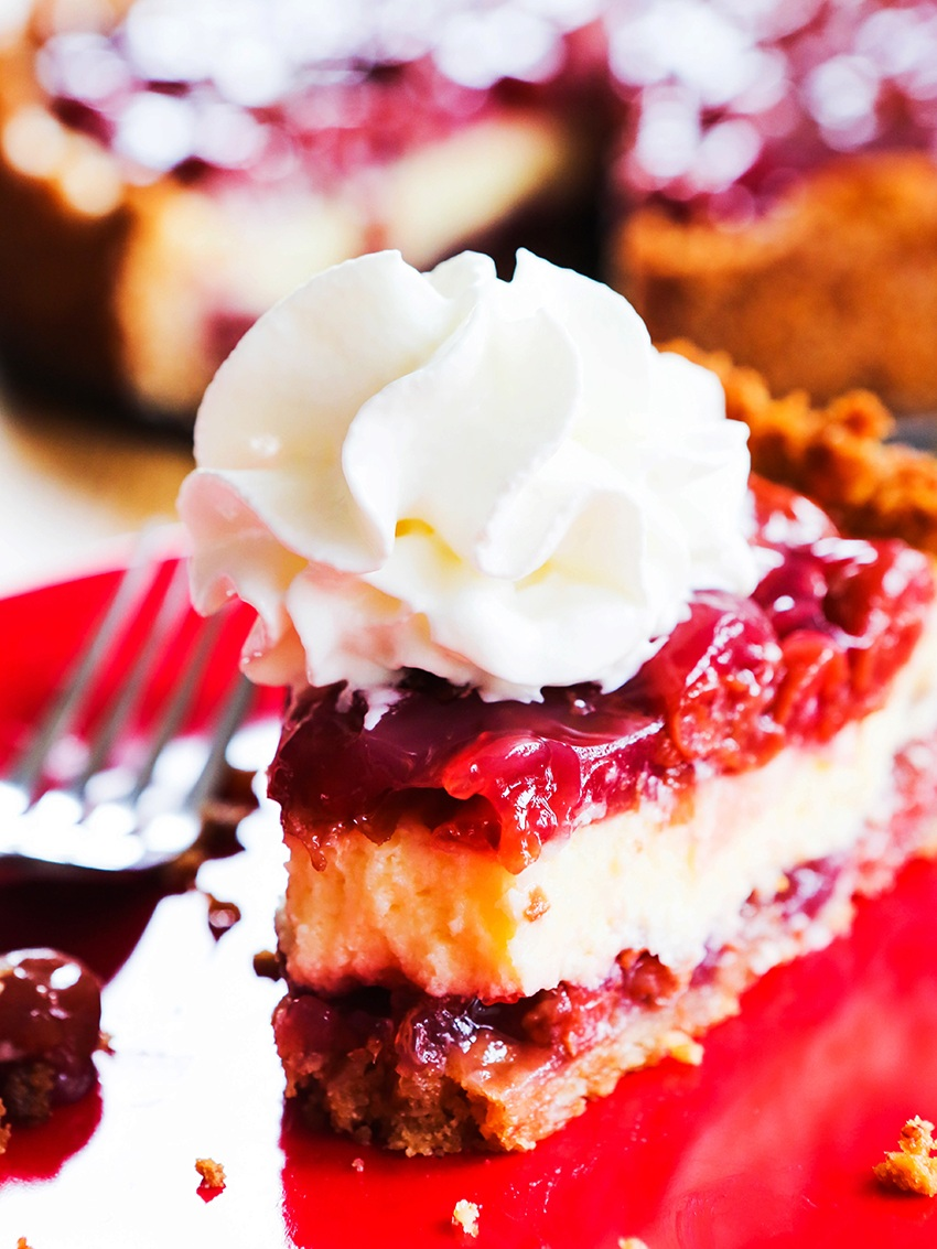 slice of baked cherry cheesecake topped with whipped cream
