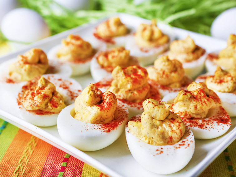 White serving platter filled with a layer of deviled eggs sprinkled with paprika