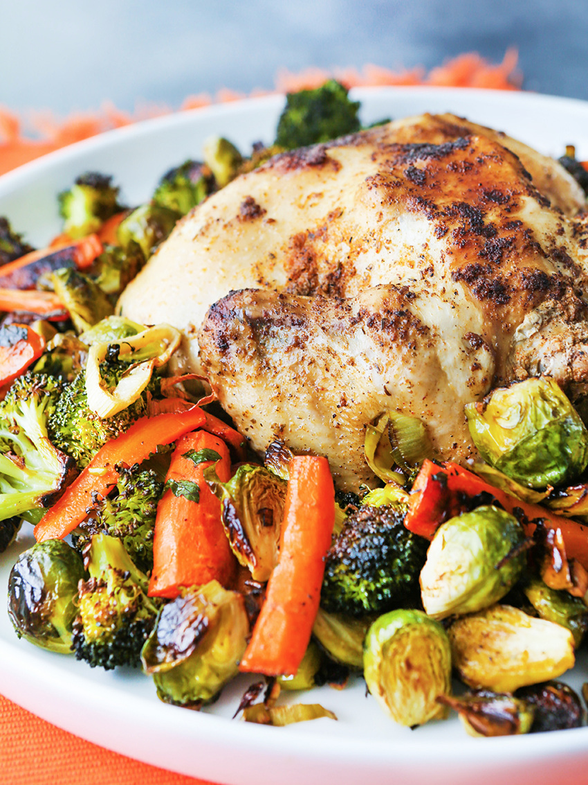 Whole chicken on serving platter with carrots and brussels sprouts