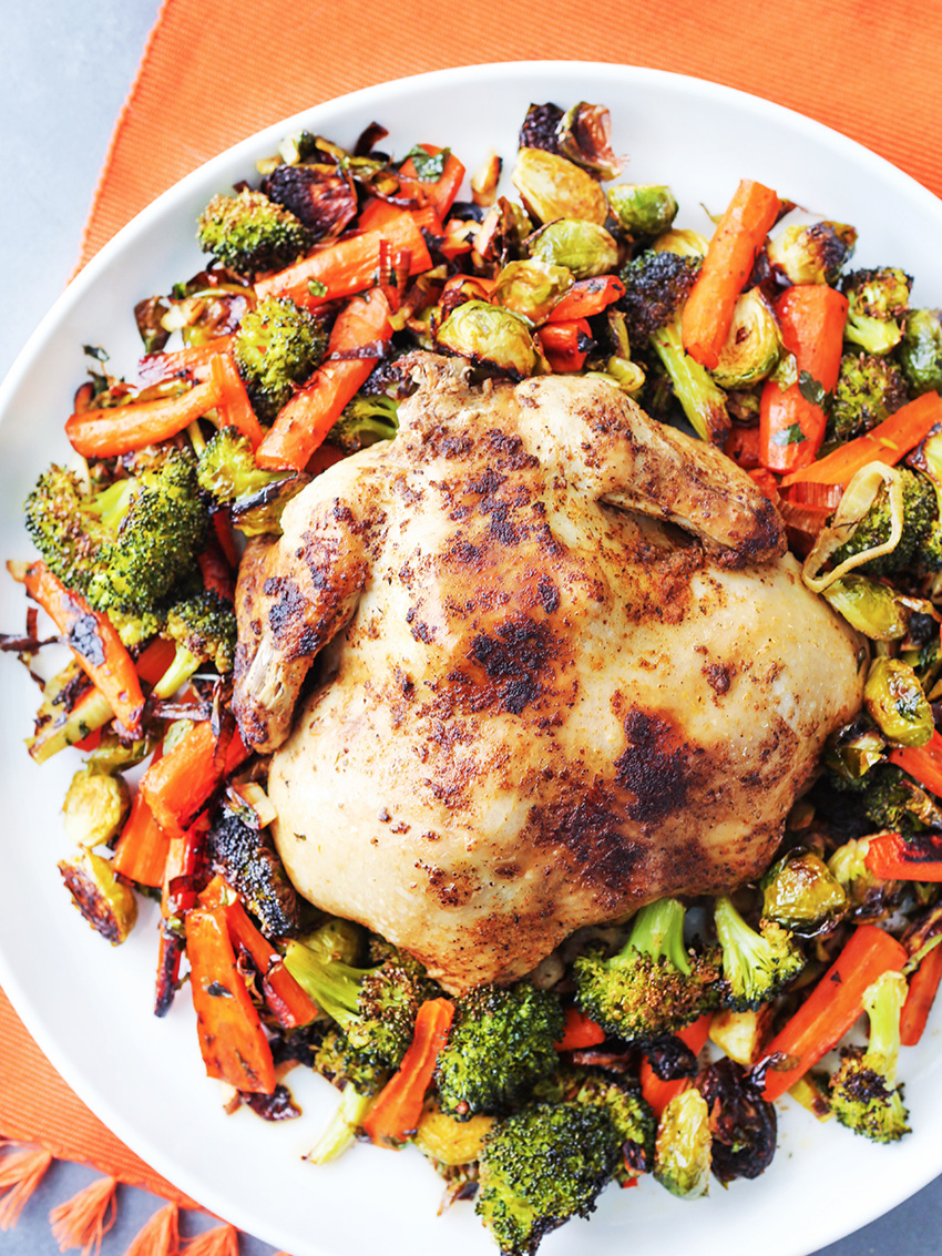 Top view of whole chicken surrounded by roasted vegetables