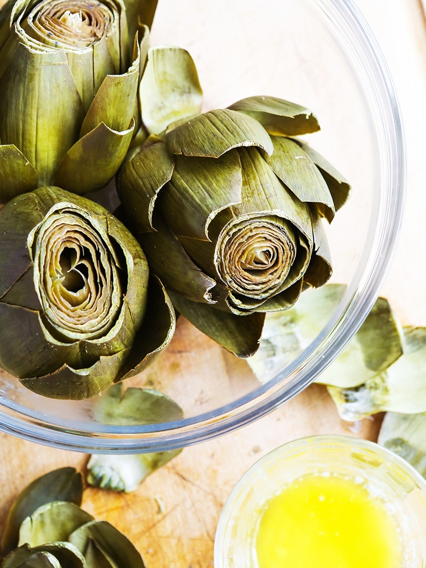 top view of bowl of cooked Instant Pot Artichokes sitting next to melted butter