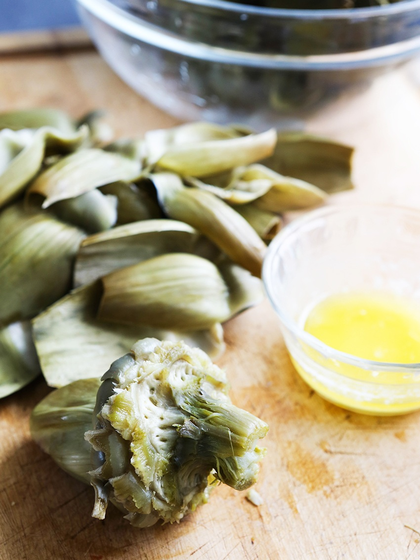 Artichoke heart next to leaves that have been removed