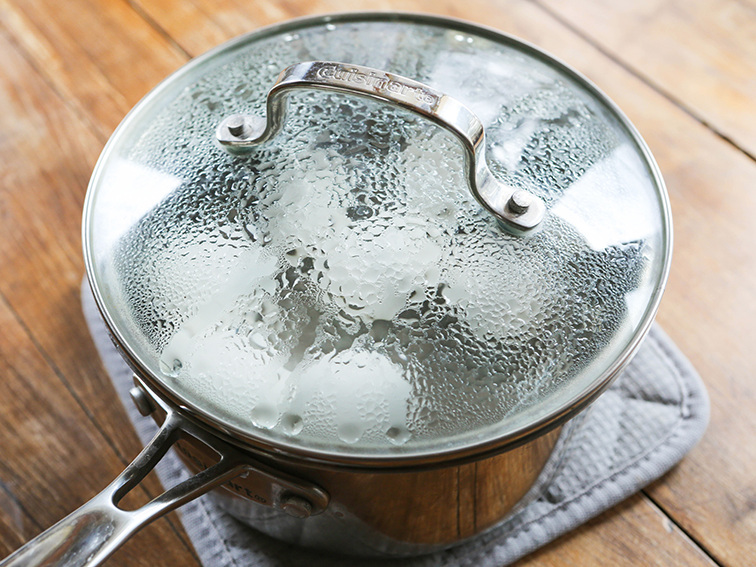 Pan of hot water sitting on a pot holder with a steamed cover on it