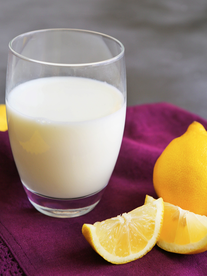 Glass of buttermilk with slices of lemon lying in front of it
