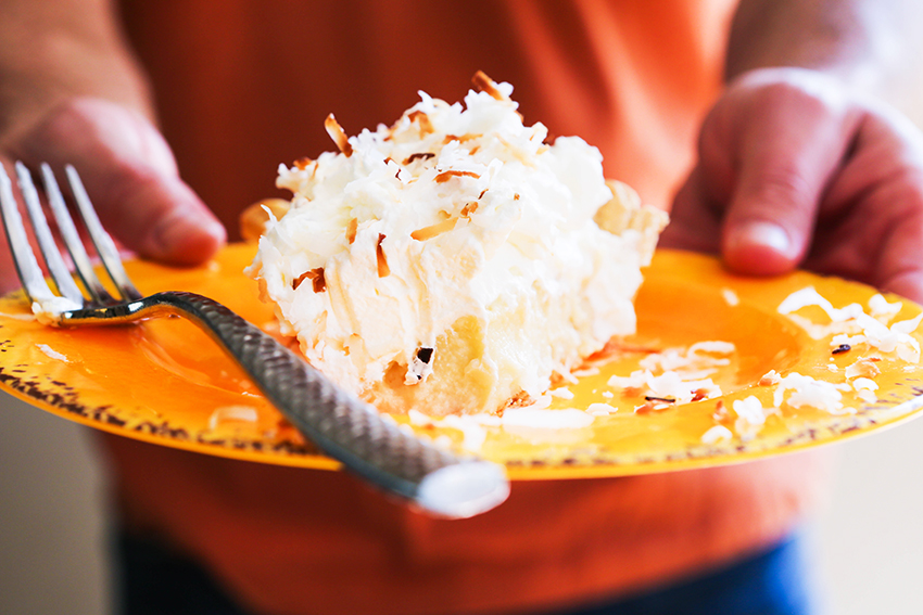 Two hands holding coconut cream pie on a plate
