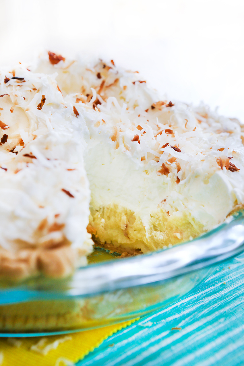 Coconut cream pie in pie pan with a slice removed