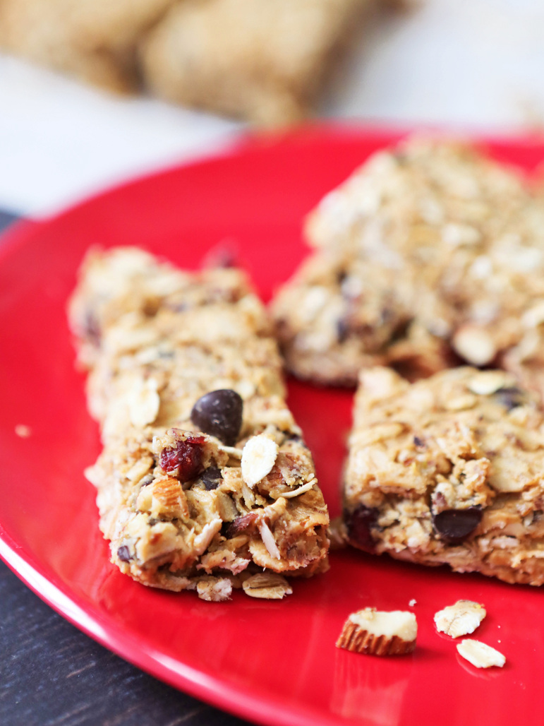 Granola bars sitting on a red plate next to stray almonds