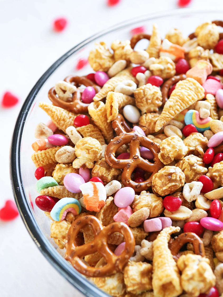 bowl filled with snack mix ingredients including pretzels, bugles and colored M&M's