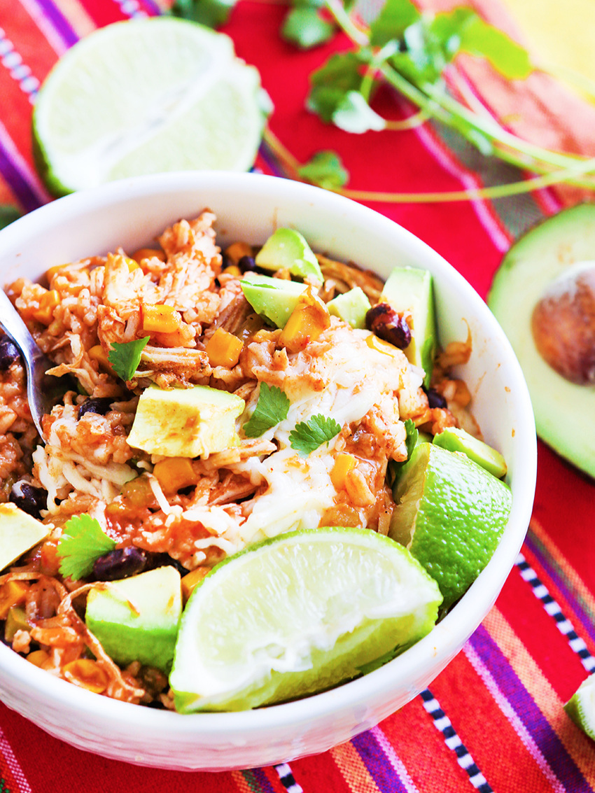 Chicken burrito bowl with avocado pieces and a lime wedge