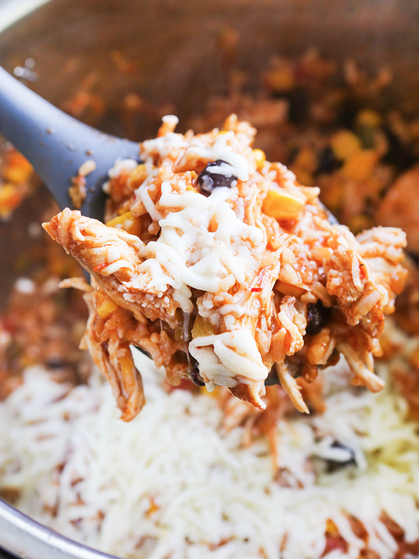 Spoonful of cheesy burrito bowl mixture hovering over Instant Pot