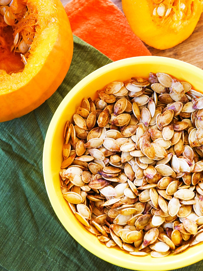 bowl of pumpkin seeds roasted next to an open pumpkin