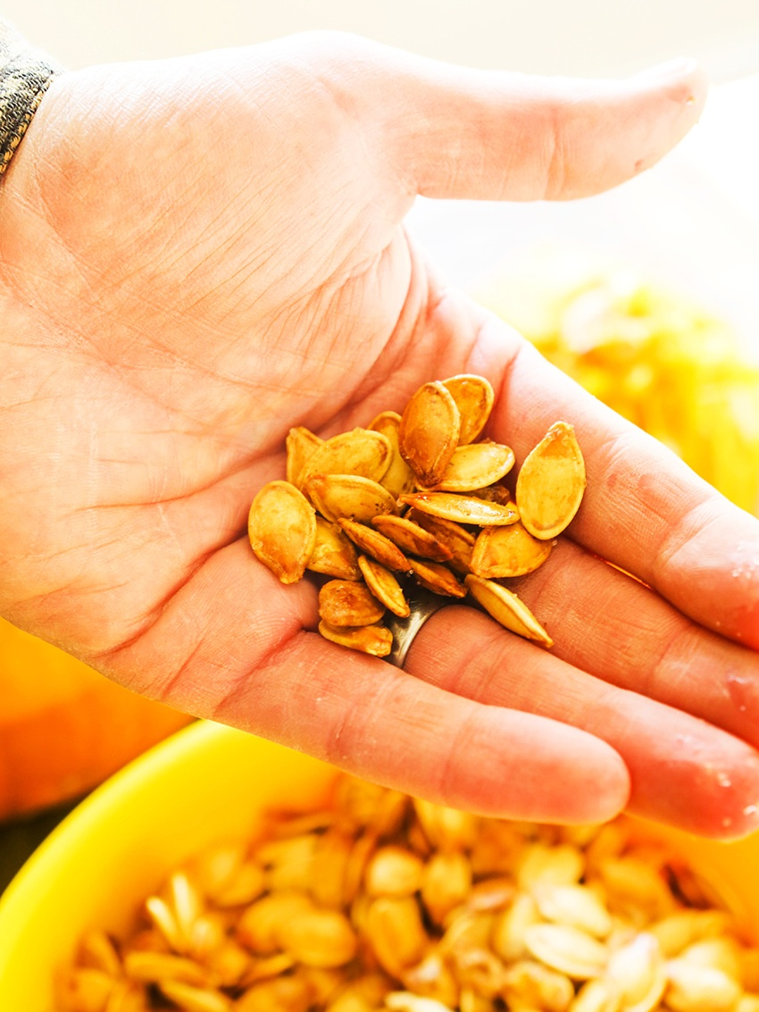 roasted pumpkin seeds held in a hand over a bowl of seeds
