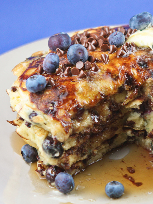 stack of pancakes topped with blueberries and chocolate chips